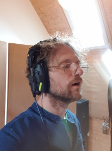 Storyteller at the microphone in a recording studio